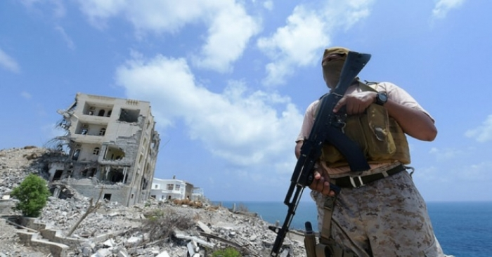 A Saudi military member stands next to a destroyed building in Aden, Yemen. (Photo: Ahmed Farwan/flickr/cc)
